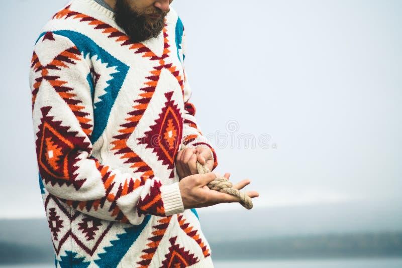 Mains d'homme tenant le mode de vie de voyage de noeud de corde images stock
