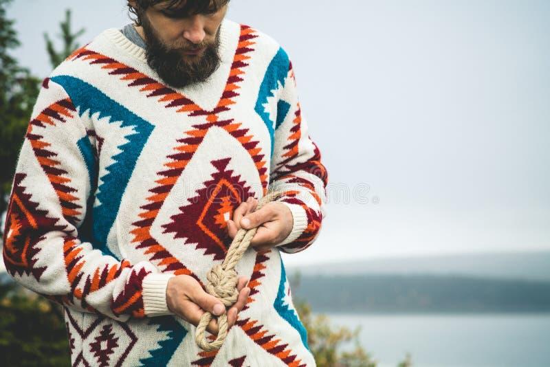 Mains d'homme tenant le mode de vie de voyage de noeud de corde photo stock