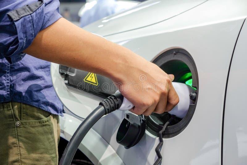 Mains d'hommes de l'Asie qui alimentent une nouvelle électrification de véhicule par l'intermédiaire de la machine rechargeable d photos libres de droits