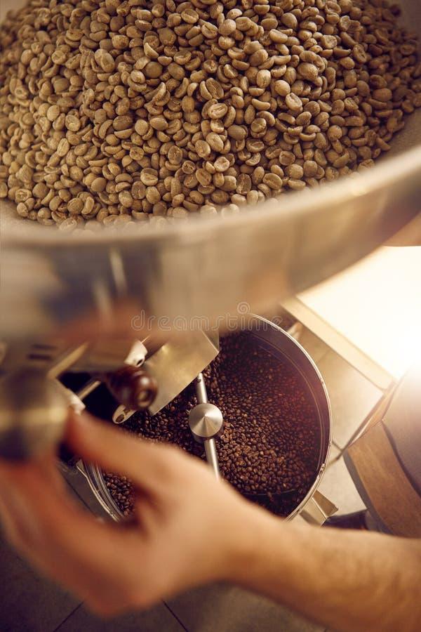 Mains d'un brûleur de café actionnant un appareil avec des haricots photos stock