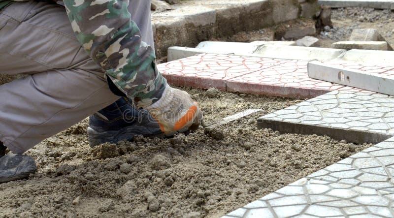 Mains d'un constructeur étendant de nouveaux pavés plaçant soigneusement un en position sur une base nivelée et ratissée de sable images libres de droits
