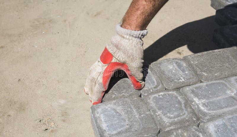 Mains d'un constructeur dans des ses mains enfilées de gants oranges s'adaptant étendant de nouveaux pavés extérieurs plaçant soi photographie stock libre de droits