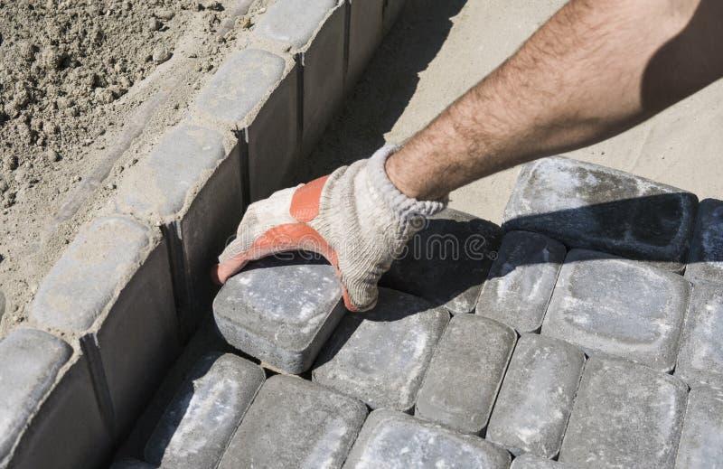 Mains d'un constructeur dans des ses mains enfilées de gants oranges s'adaptant étendant de nouveaux pavés extérieurs plaçant soi images stock