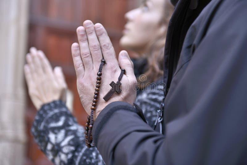 Mains d'un couple de prière retenant des petits programmes de prière photographie stock libre de droits