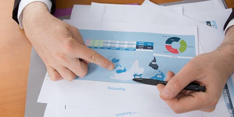mains d'un homme d'affaires analysant ses ventes internationales images stock