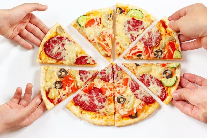 Mains d'un homme et d'un enfant se cassant vers le haut des morceaux de pizza aromatisée image libre de droits