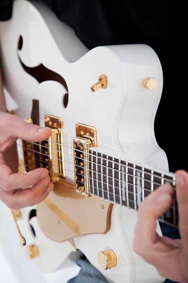 Mains d'un homme jouant une guitare électrique photos stock