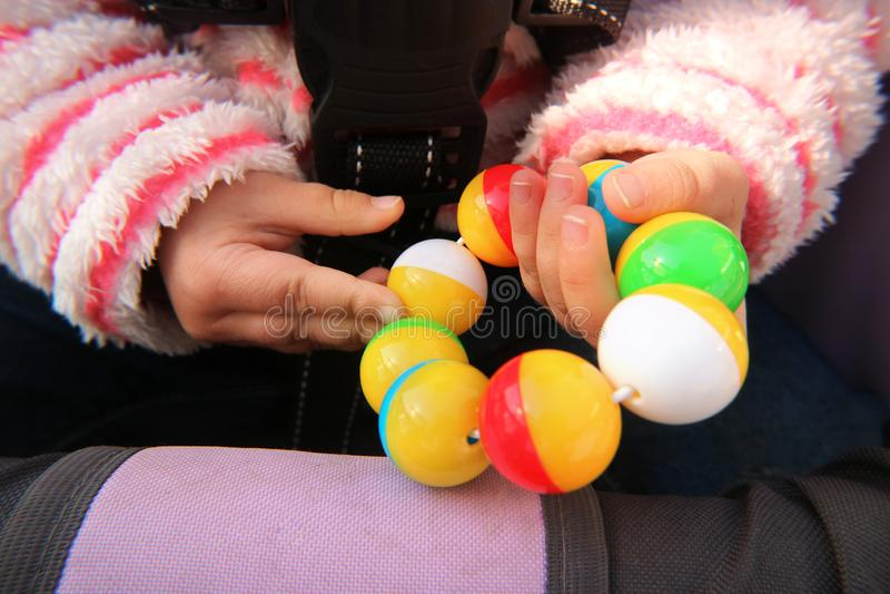 Mains d'un petit enfant tenant un jouet en plastique de hochet photographie stock libre de droits