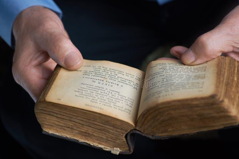 Mains d'un vieil homme tenant un livre avec des textes des chansons religieuses dans le polonais photos stock