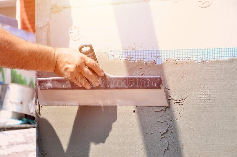 Mains d'un vieux travailleur manuel avec le mur plâtrant des outils rénovant la maison images libres de droits