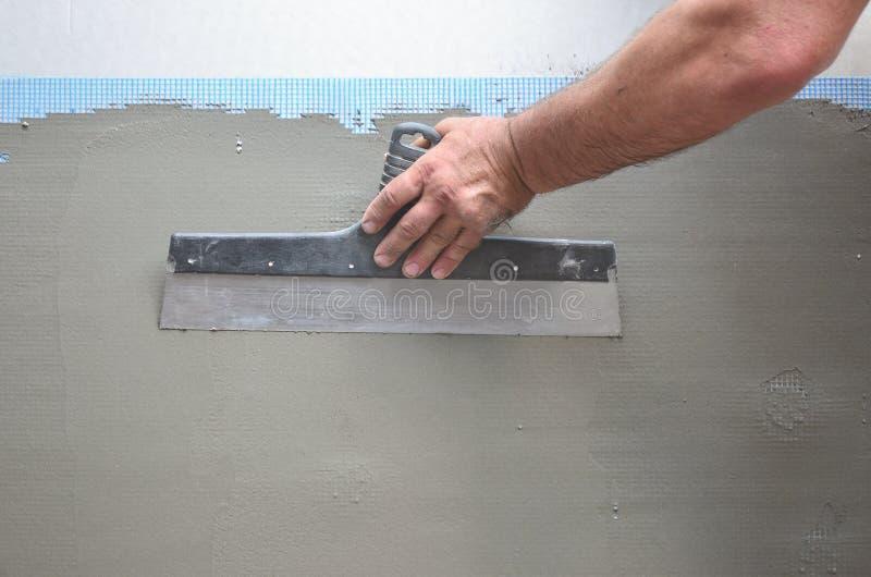 Mains d'un vieux travailleur manuel avec le mur plâtrant des outils rénovant la maison Plâtrier rénovant les murs et les coins ex photos stock