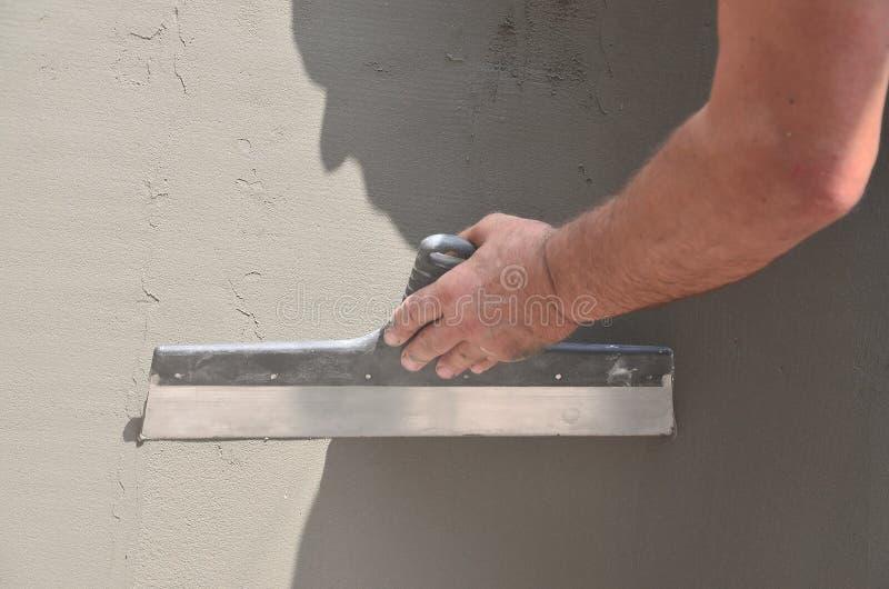 Mains d'un vieux travailleur manuel avec le mur pl?trant des outils r?novant la maison Pl?trier r?novant les murs et les coins ex images stock
