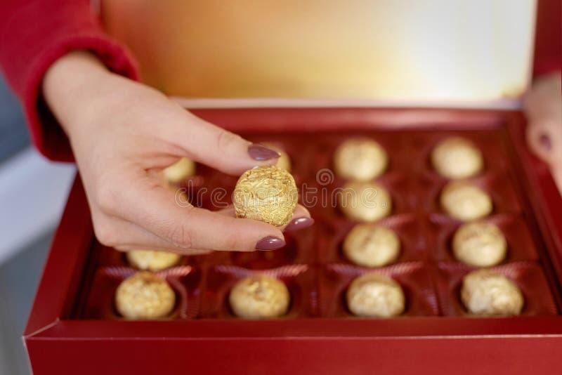 Mains d'une boîte de participation de femme avec des bonbons au chocolat Concept heureux de cadeau de valentines images libres de droits