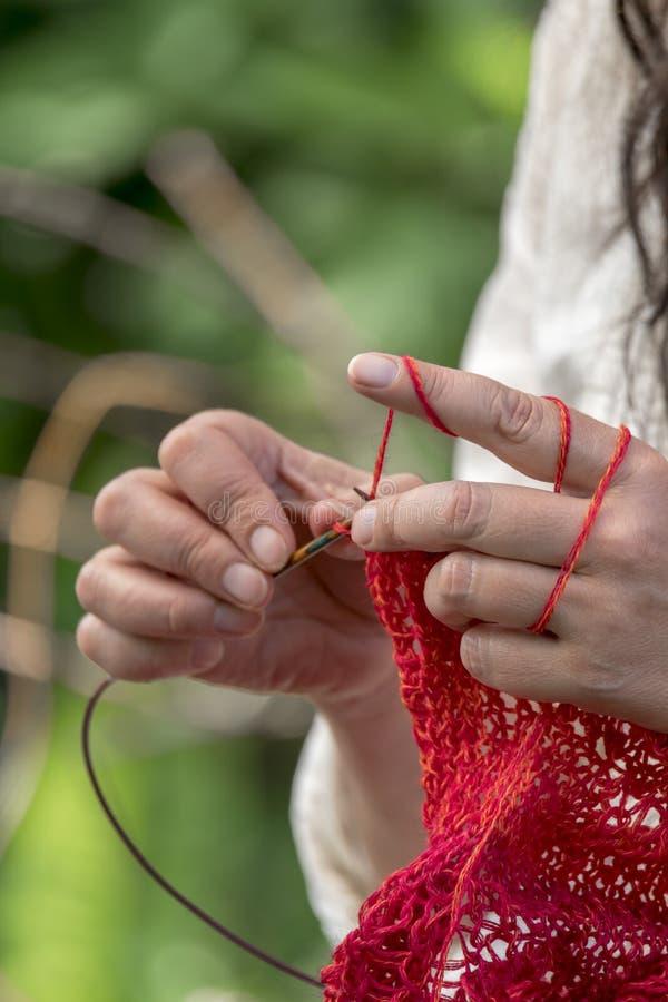 Mains d'une femme qui fait du crochet avec la laine/knits rouges photographie stock libre de droits