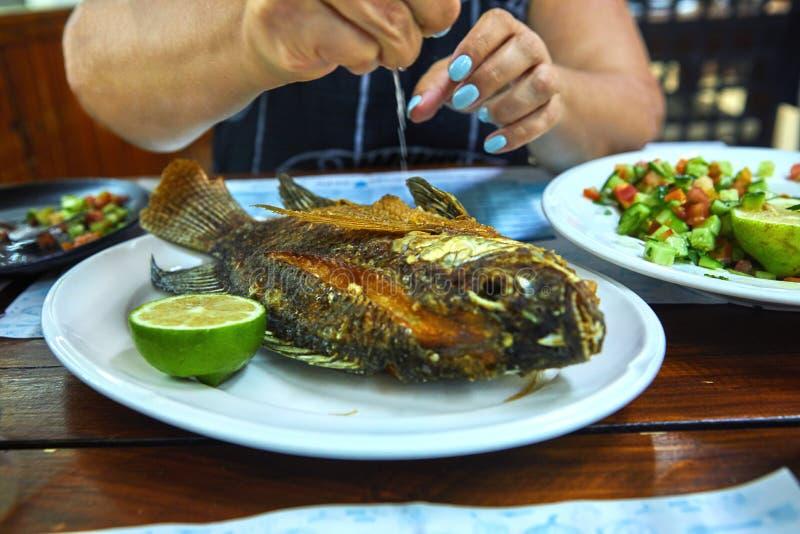 Mains d'une femme tenant un citron et versant les poissons frits sur un restaurant d'esclave de plat images stock