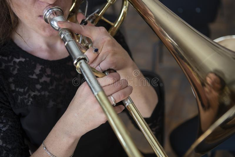 Mains d'une fille jouant le trombone photo stock