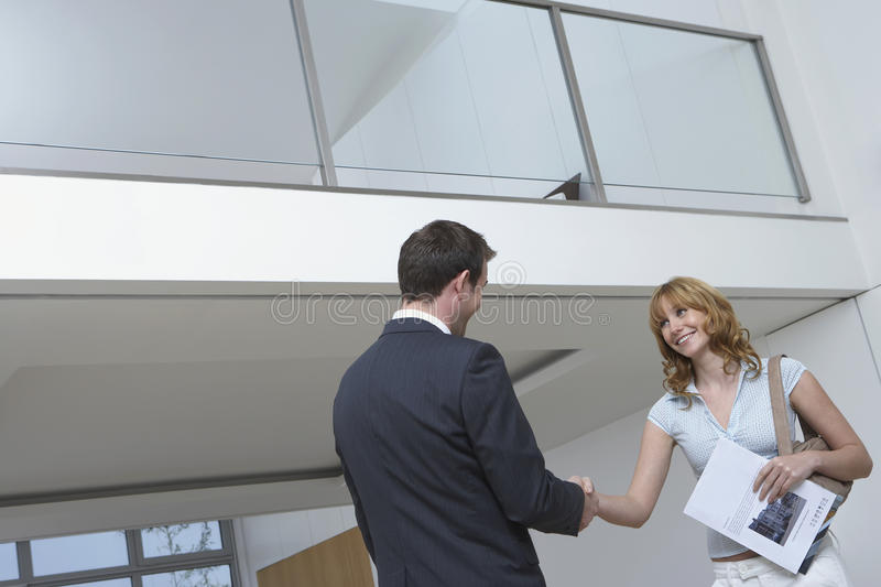 Mains d'And Woman Shaking d'agent de Real Estate dans la nouvelle maison photographie stock