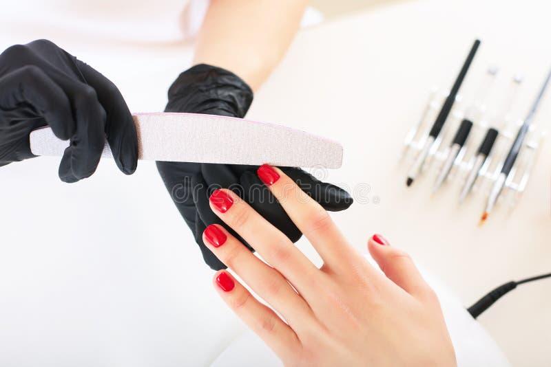 Mains dans des soins de gants au sujet des clous de mains Salon de beauté de manucure images libres de droits