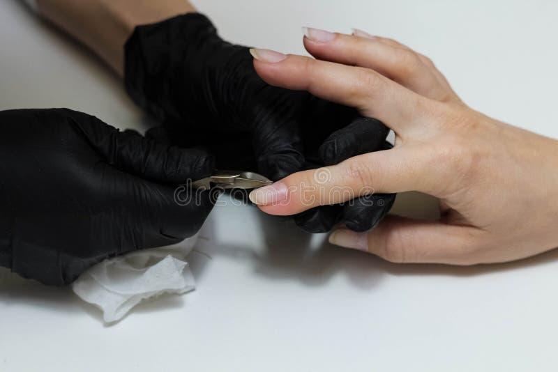 Mains dans des soins noirs de gants au sujet des clous de mains Salon de beaut? de manucure Classement de clous avec le dossier photographie stock libre de droits