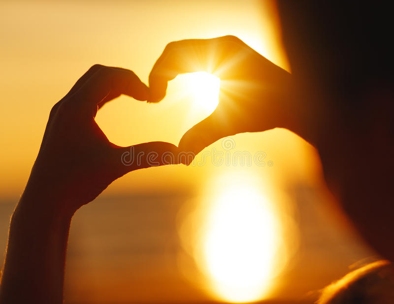 Mains dans la forme du coeur au coucher du soleil sur la plage photographie stock