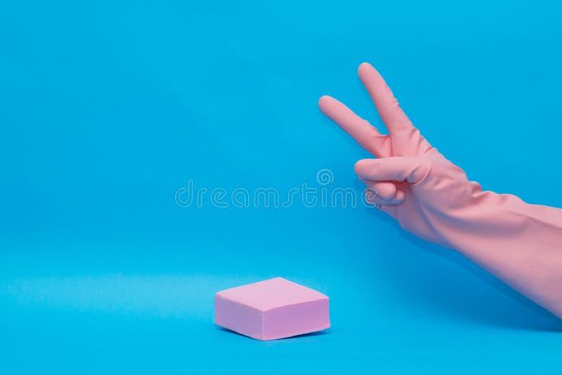 Mains dans le gant rose économique pour des produits domestiques sur le fond bleu pour la conception image stock