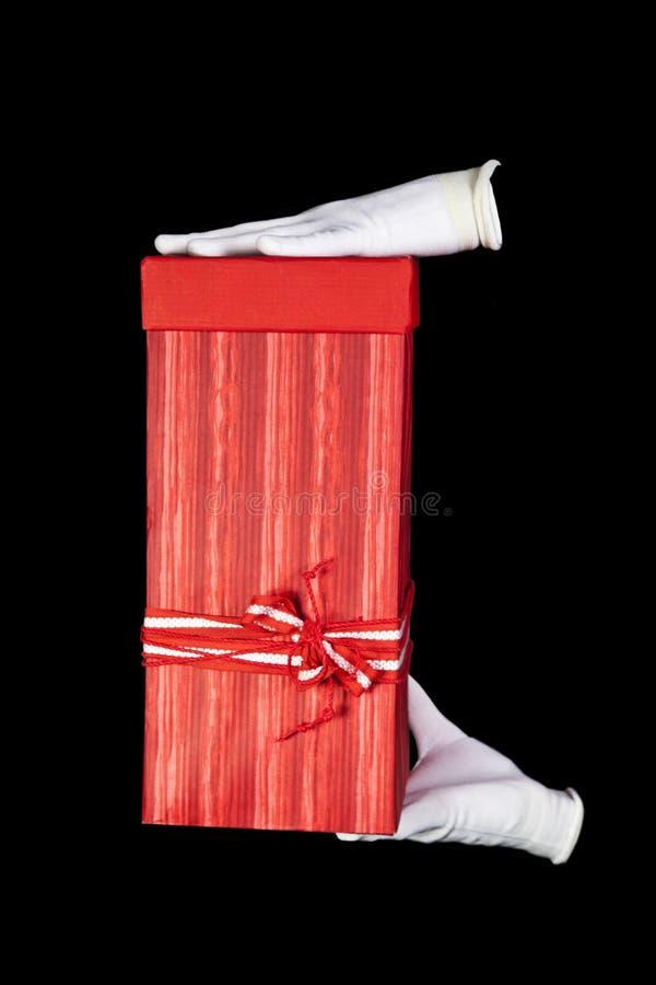 Mains dans les gants blancs avec le cadre de cadeau rouge photo stock