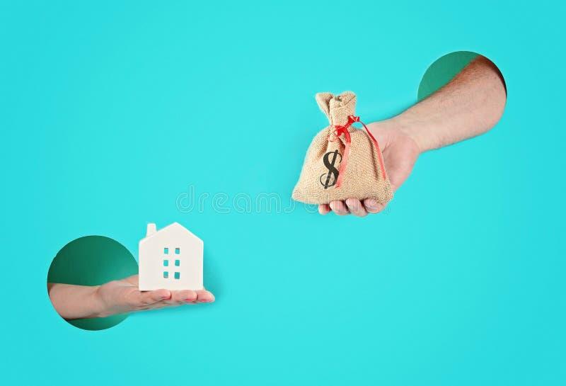 Mains dans les trous de papier tenant la maison et un sac avec l'argent photo stock