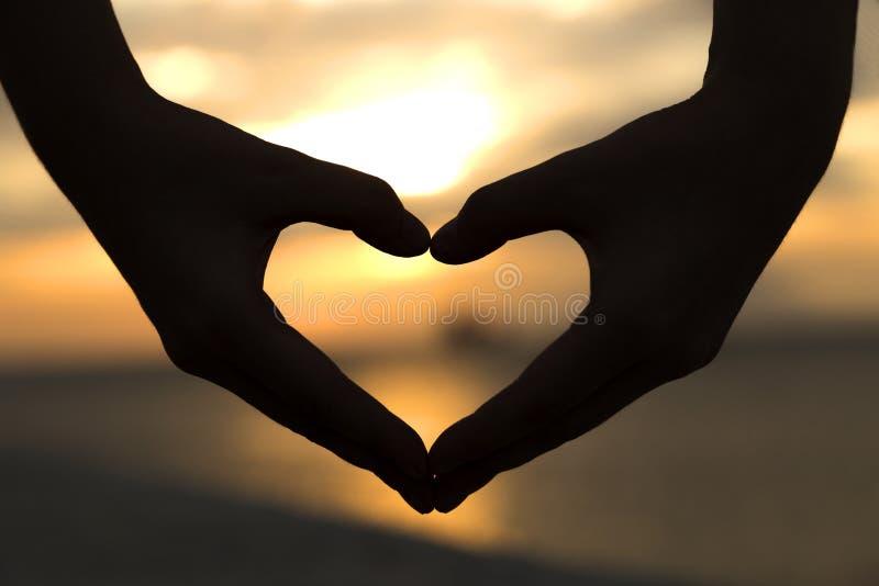 Mains dans une forme de coeur, exprimant l'amour images libres de droits