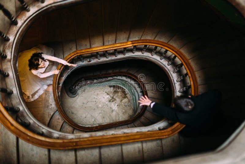 Mains de élargissement de couples élégants de mariage entre eux à la vieux maison et palais de vintage avec de grands escaliers e image libre de droits