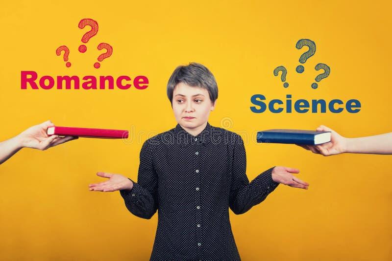 Mains de équilibrage perplexes d'étudiante de jeune femme pensant quoi lire entre un livre de la science et roman Dilemme bien ch photo libre de droits