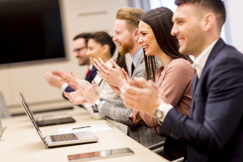 Mains de applaudissement de sourire heureuses d'équipe d'affaires photographie stock libre de droits