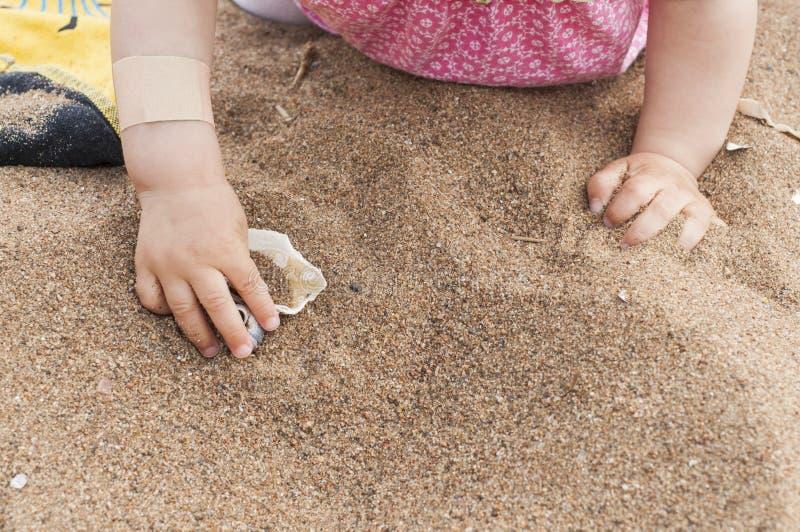 Mains de bébé atteignant pour un coquillage Bébé dans le rose jouant sur une plage sablonneuse Prendre un bain de soleil de bébé photo libre de droits