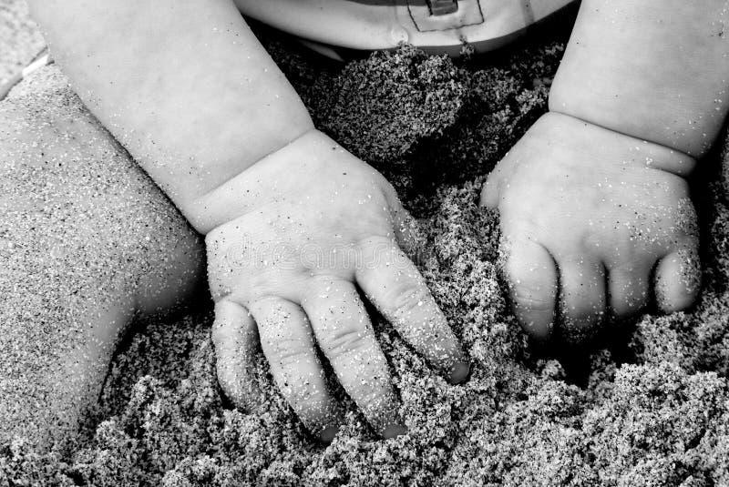 Mains de bébé dans le sable photographie stock