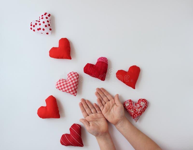 Mains de bébé tenant de petits coeurs rouges photos libres de droits