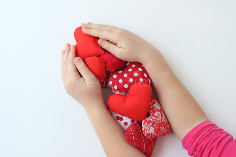 Mains de bébé tenant de petits coeurs rouges photo stock