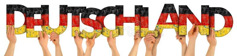 Mains de bras de personnes retardant le lettrage en bois de lettre formant le mot Deutschland dans la nation allemande de voyage  photos stock