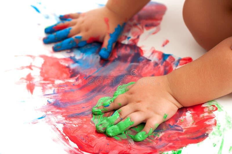 Mains de chéris peignant la mosaïque colorée. photographie stock