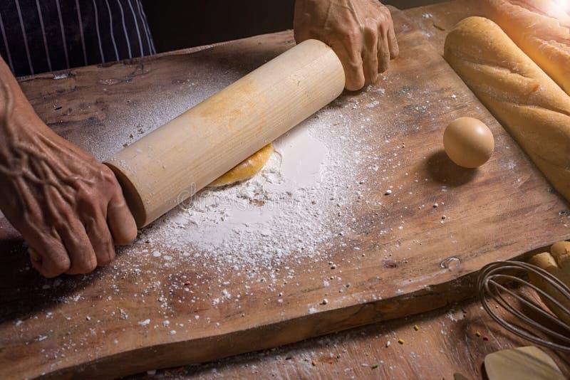 Mains de chef malaxant la p?te pour la boulangerie Fabrication de la p?te par les mains masculines ? la boulangerie Homme malaxan image stock