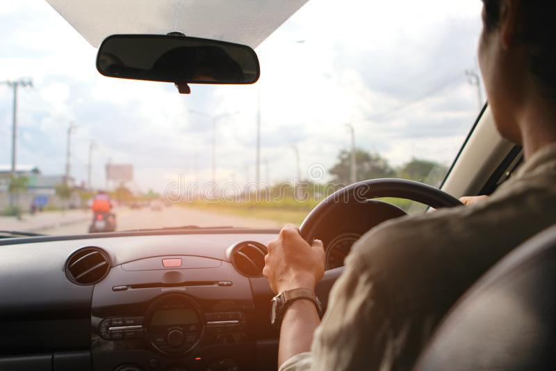 Mains de conducteur d'homme tenant le panneau de direction de voiture photographie stock