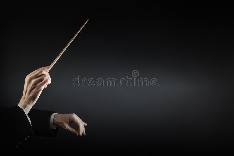 Mains de conducteur de musique avec le bâton images stock