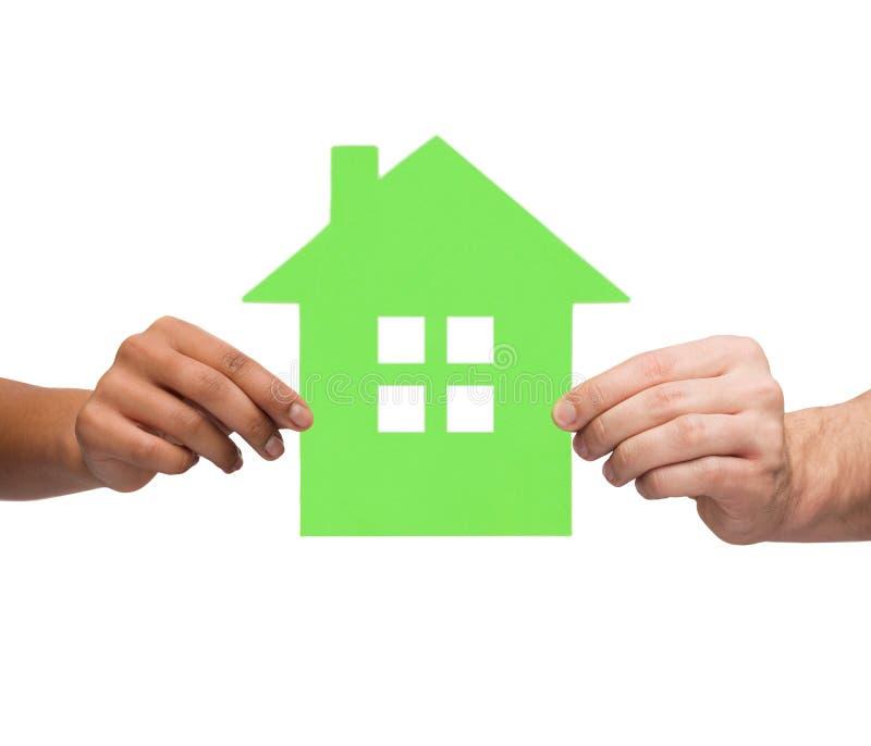 Mains de couples tenant la maison verte photo stock
