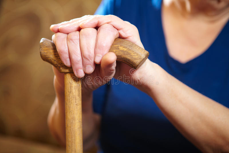 Mains de dame âgée avec la canne image stock
