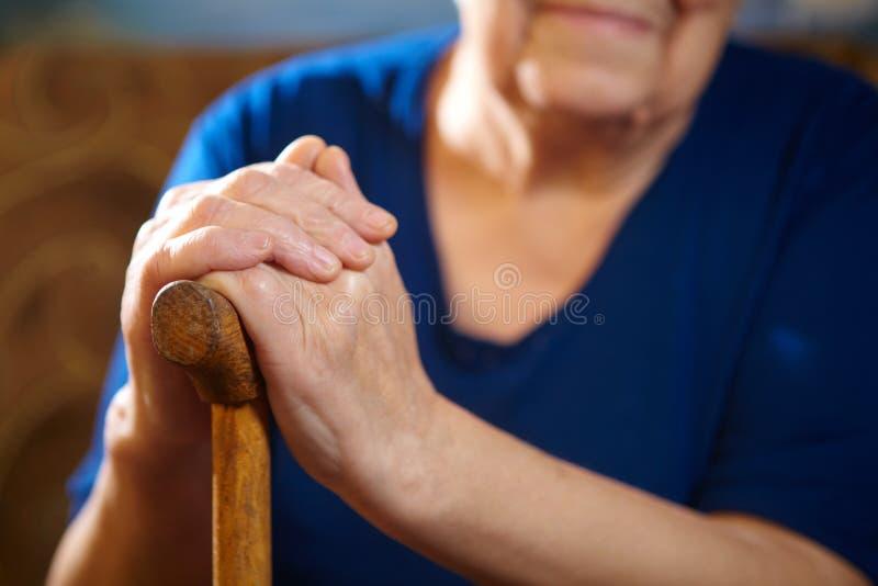 Mains de dame âgée avec la canne photo stock