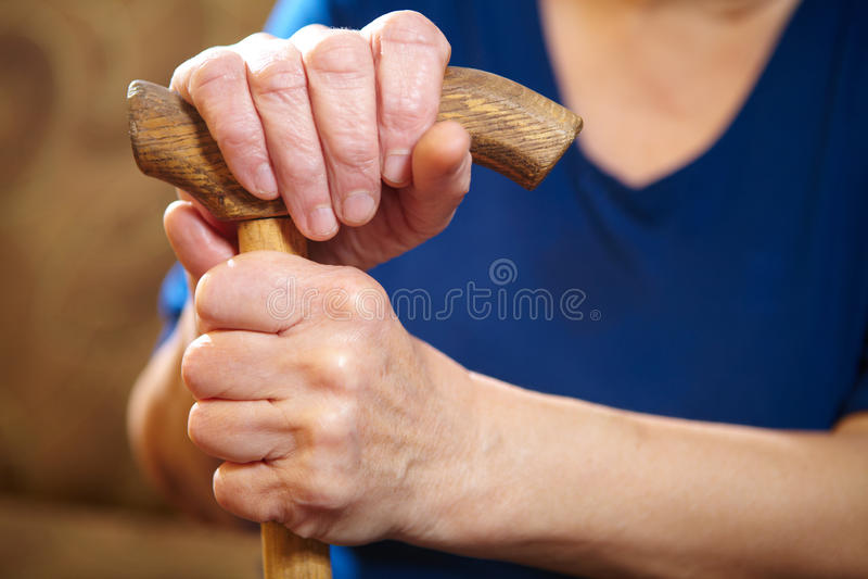 Mains de dame âgée avec la canne photos stock