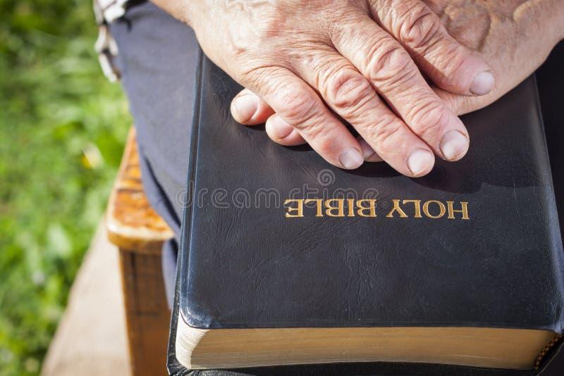 Mains de dame âgée sur la Sainte Bible images libres de droits