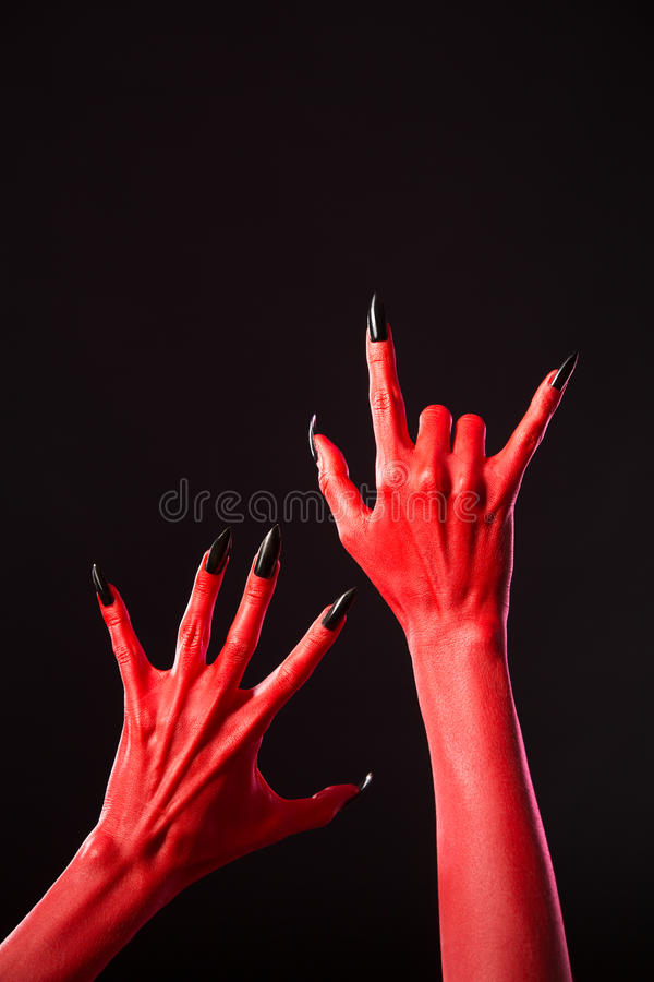 Mains de diable rouge avec de longs clous noirs, vrai corps-art images libres de droits