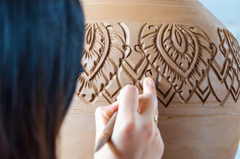 Mains de faire le pot d'argile sur la roue de poterie, foyer choisi, plan rapproché photos libres de droits