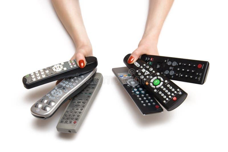 Mains de femme avec des contrôles de TV photos stock
