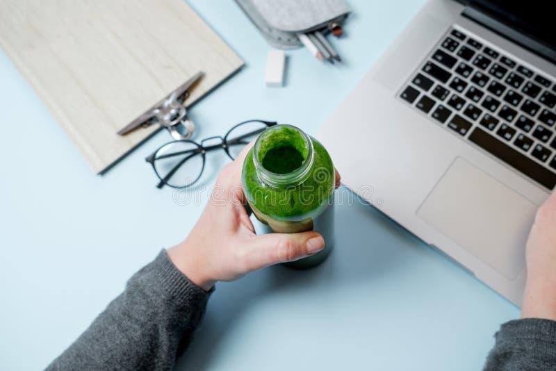 Mains de femme avec l'ordinateur portable et les smoothies verts avec la pomme sur t bleu photographie stock