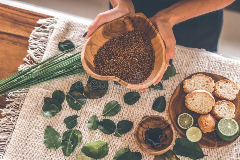 Mains de femme avec la cuvette en bois de teck avec le gruau de sarrasin sur la table Nourriture russe traditionnelle Chaux et pa photo stock